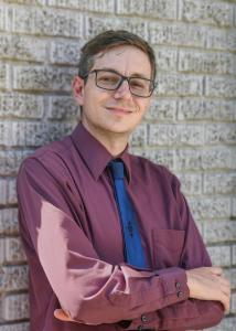 Smith with short hair, glasses and blue tie