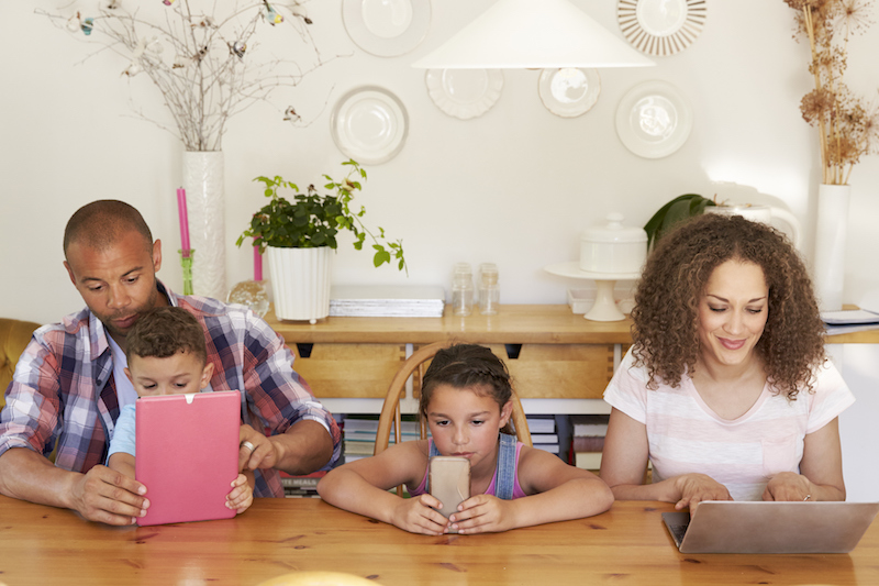 Photo of a family sitting at the table, all with electronic devices in front of them.