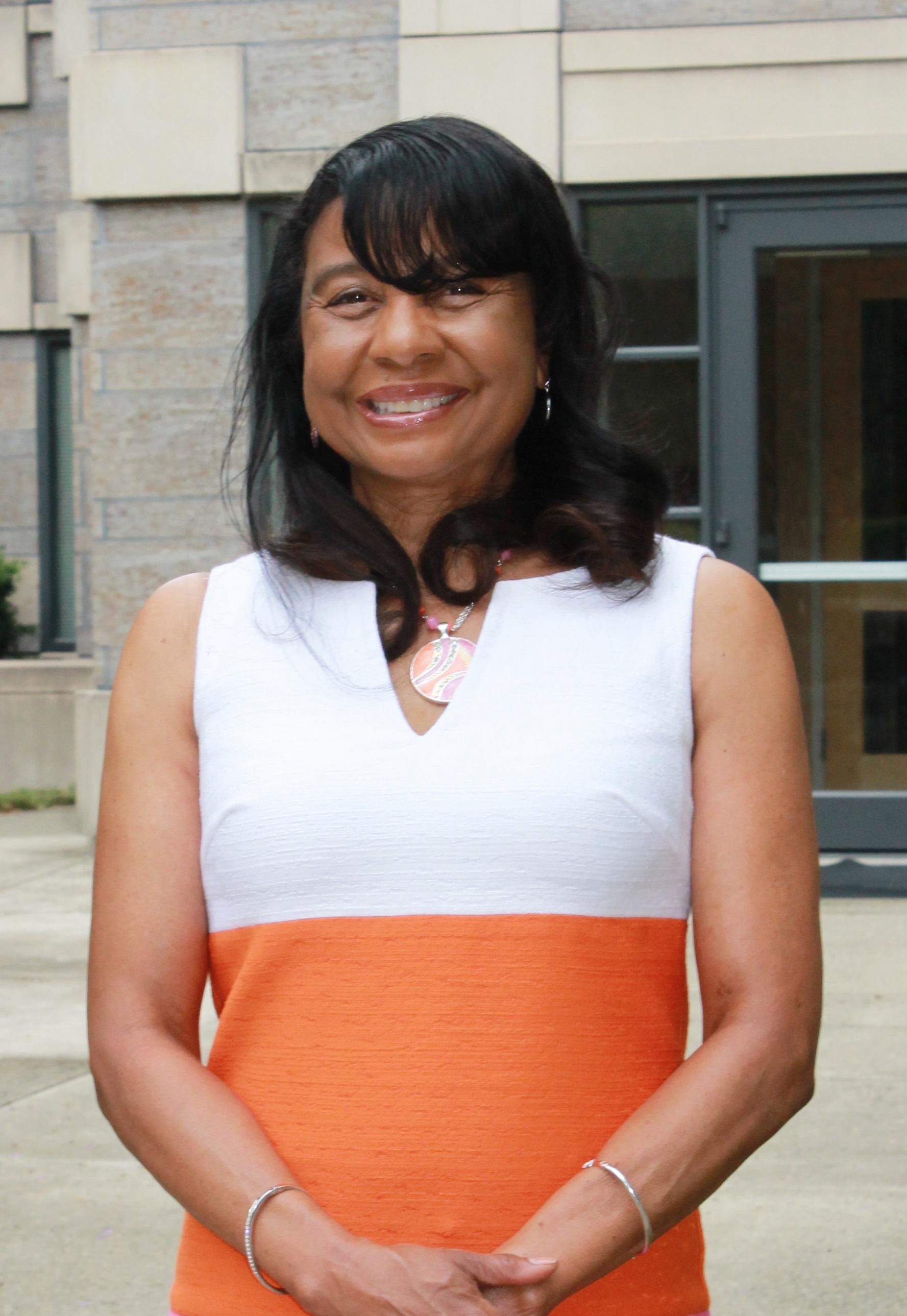 Photo of Linda Burton with long black hair and white and orange dress.