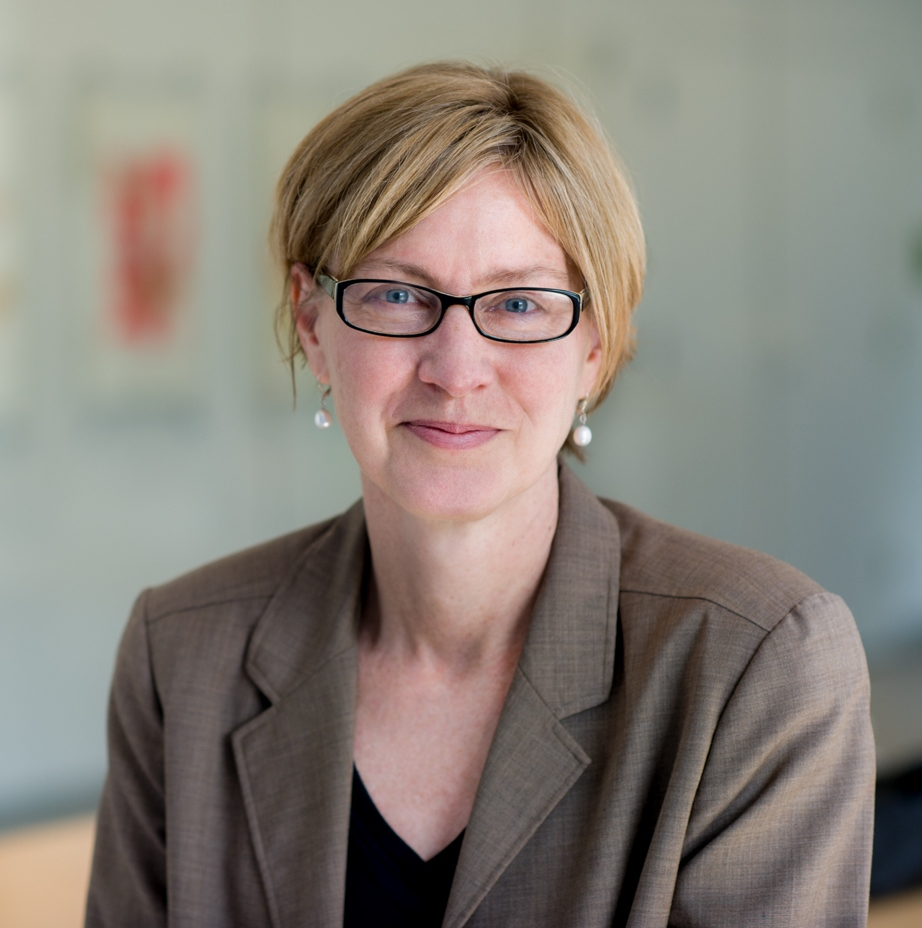 Photo of Susan Short with short blond hair, wearing black rimmed glasses, white pearl earrings, and a brown blazer. (From her bio on Brown University's website.)