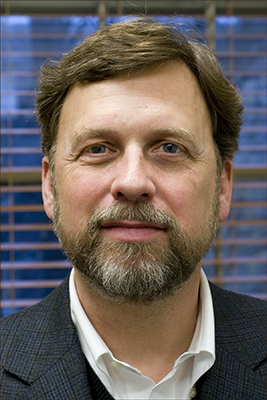 Lindstrom with brown hair, beard and mustache and white shirt
