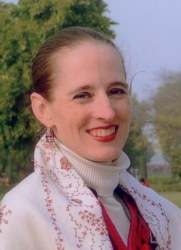 Headshot of Mary Shenk with brown, pulled back hair, white turtleneck, red sweater, and white and red scarf.