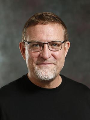 Headshot of Sam Clark with short brown hair, gray beard, glasses, and black shirt.