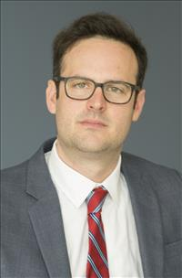 Headshot of Daniel Max Crowley with brown hair, glasses, white shirt, red and white striped tie, and gray jacket.