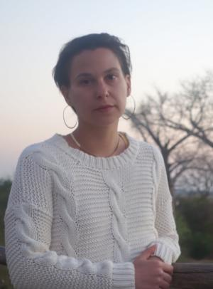 Headshot of Jennifer Trinitapoli with short dark hair, hoop earrings, and white sweater.