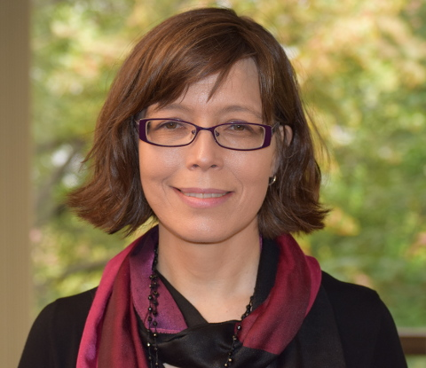 Headshot of Emily Hannum with short brown hair, glasses, black top, and red scarf.