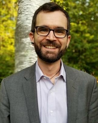 Headshot of Jason with brown hair, beard, glasses, purple shirt, and gray jacket.