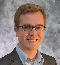 Headshot of Matthew Hall with blond hair, glasses, white shirt, and gray jacket.