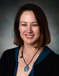 Lisa Gatzke-Kopp headshot in short brown hair and black shirt with blue necklace.