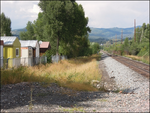 Rural location with trailers and railroad tracks.