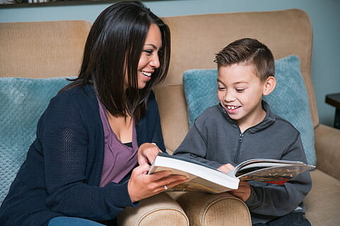 Mom and son looking at a book together smiling while sitting on a tan couch with blue pillows.