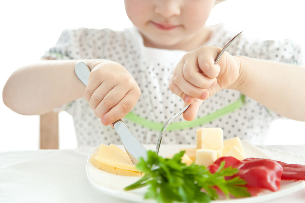 Young child eating a plate of fruit and vegetables