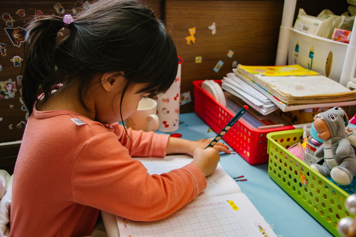 Young girl with black pony tail and orange shirt completing worksheet in school