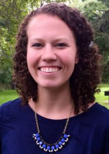 Headshot of Allison Gray with brown curly hair and dark blue blouse.