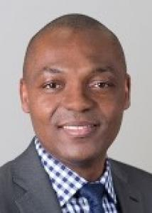 Sunday Azagba head shot in dark gray suite, blue and white checkered shirt, blue tie, smiling with short black hair.