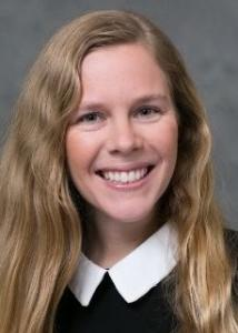 Brandy Henry headshot with long blonde hair and black shirt with white collar.