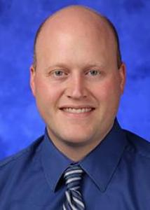 Headshot of Brian Allen wearing a navy shirt with a blue and white striped tie.