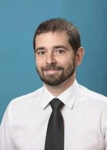 Headshot of Chad Shenk with short brown hair, a beard, a white shirt, and a black tie.