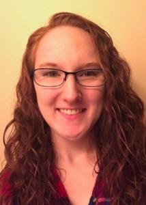 Headshot of Chelsea Dickens with long red hair, glasses, and red top.