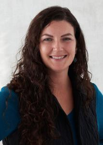 Headshot of Cheryl Stamm with long curly dark hair in blue sweater.
