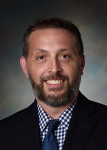 Headshot of Christian Connell with a beard, white and navy checkered shirt, navy tie, and black jacket.