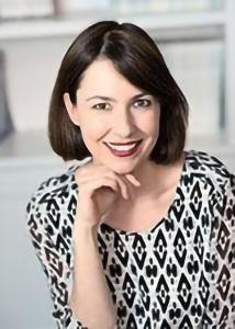 Headshot of Christine Heim with short dark brown hair and a black and white patterned top.