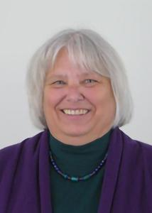 Headshot of Cynthia Mitchell with mid-length grey hair, green turtleneck, purple cardigan and matching necklace.