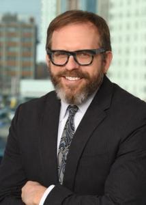 Headshot of Craig Newschaffer with brown hair, beard, glasses, white shirt, gray swirled tie, and black jacket.