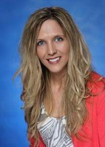 Headshot of Danielle Downs with long blonde hair, white and gray shirt, and pink jacket.