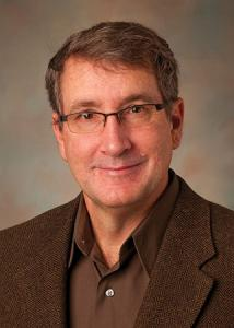 Headshot of David Almeida in a brown dress shirt and jacket wearing glasses.
