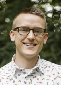 Headshot of David Lydon-Staley with blonde hair, glasses, and white shirt with colorful graphics.
