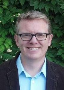 Headshot of Derek Kreager outside with glasses and light-colored hair wearing a blue dress shirt and black suit jacket
