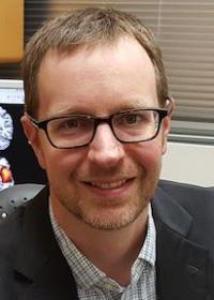 Eric Claus headshot in glasses and black blazer.