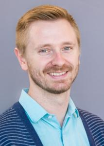 Headshot of Eric Layland with blonde hair, beard, light blue shirt, and blue and white striped sweater.