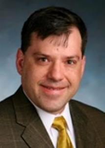 Headshot of Gregory Shearer with short black hair, white shirt, gold tie, and brown jacket.