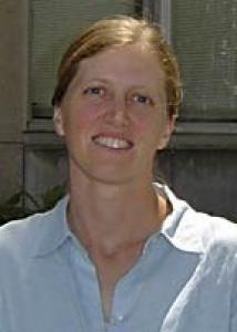 Headshot of Jenae Neiderhiser with pulled back hair and light blue top.
