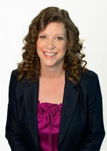 Headshot of Jennie Noll with long brown hair, pink top, and black jacket.