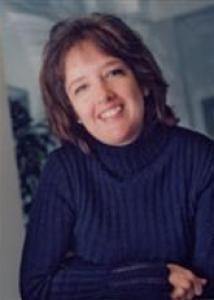 Headshot of Jennifer L. Maggs with medium dark brown hair in blue sweater.