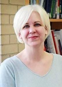 Headshot of Jenny Van Hook in front of a bookshelf with blonde hair wearing a grey shirt.