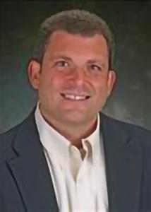 Headshot of Joshua Smyth with brown hair, white shirt, and black jacket.