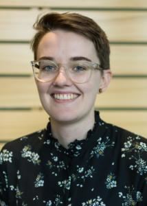 Headshot of Julie Wood with short brown hair, glasses, and black blouse with white floral print.