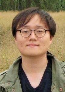 Headshot of Jungmin Lee with short dark hair, glasses, black shirt, and green jacket.