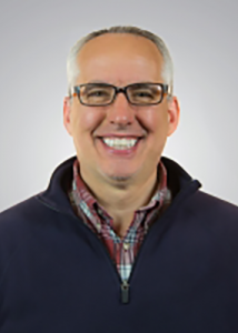 Headshot of Keith Aronson with gray hair, glasses, red plaid shirt, and navy jacket..
