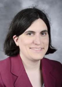 Headshot of Kelly Rulison with medium short dark hair in dark red blazer.