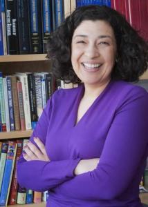 Headshot of Koraly Pérez-Edgar with black hair and purple long sleeved blouse.