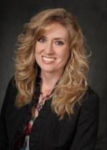 Headshot of Kristie Auman-Bauer with long blonde wavy hair, multi-colored blouse, and black jacket.