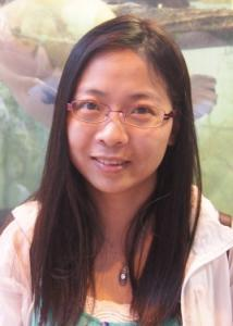 Headshot of Linying Ji with long dark hair, glasses, green and white top, and pink jacket.