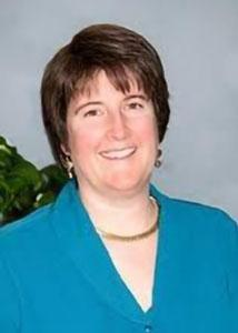 Headshot of Lisa Broniszewski with short brown hair in front of grey background wearing blue suit jacket and gold necklace.