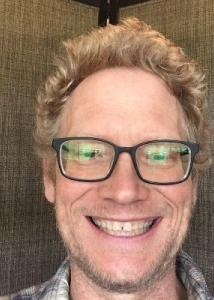 M. Luke Smith head shot with black framed glasses and blond curly hair smiling.