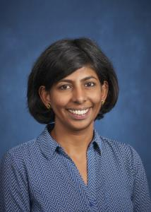 Headshot of Maithreyi Gopalan with mid-length, dark hair wearing a blue shirt in front of a blue background.